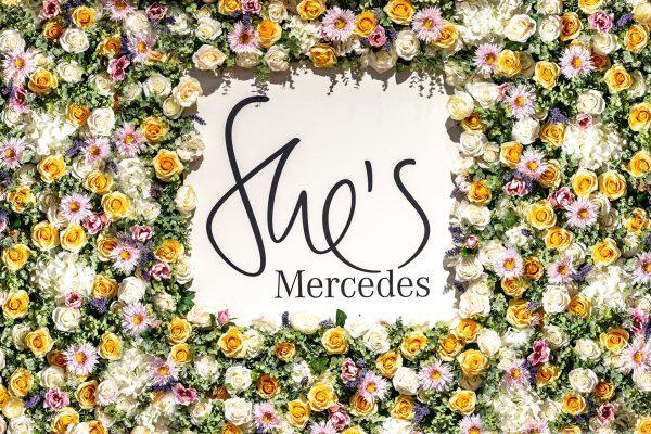 Schriftlogo von She´s Mercedes mit Blüten umrandet.